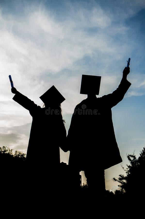 La siluetta graduata del ragazzo e della ragazza, lo studente di graduazione, la ragazza ed il ragazzo si laureano, fotografia stock libera da diritti