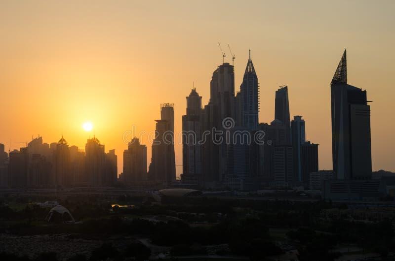 La siluetta polverosa di paesaggio urbano del tramonto del porticciolo del Dubai ha sparato dal campo da golf di verdi I verdi -  fotografia stock