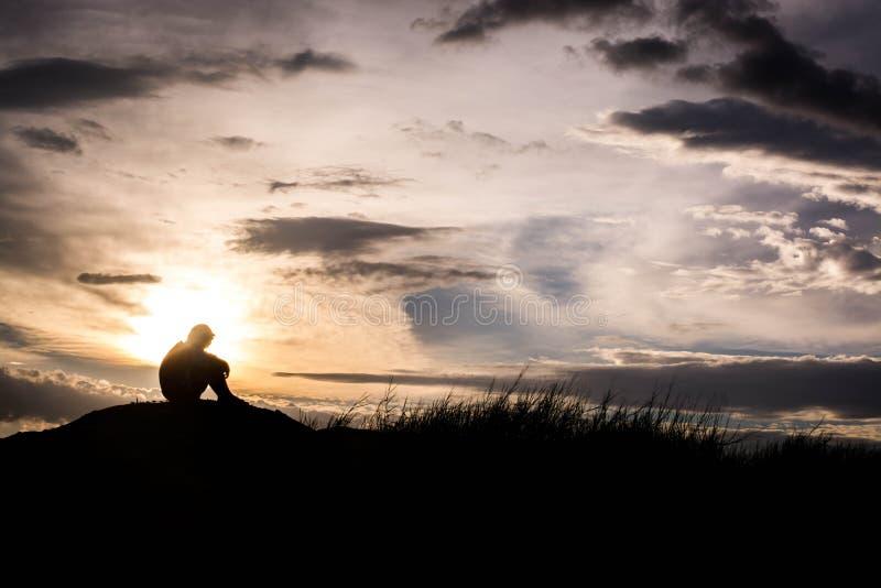 La siluetta triste del ragazzo si è preoccupata sul prato al tramonto, la siluetta c fotografia stock