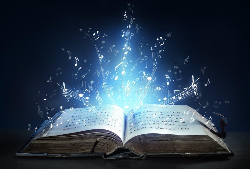 La sinfonia classica splende con le note musicali da un libro antico fotografia stock libera da diritti