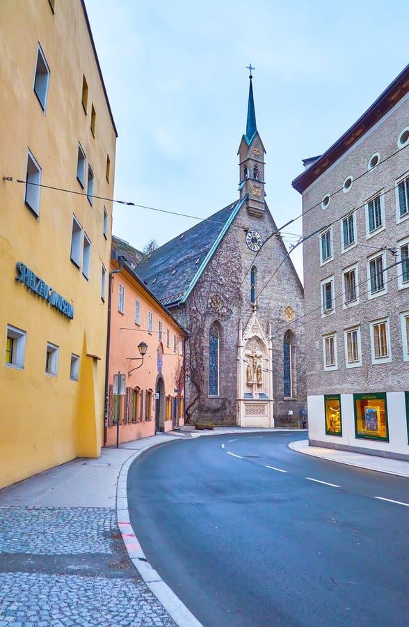 La sinuosa Bugerspitalgasse con la iglesia de St Blasius, Salzburgo, Austria fotos de archivo