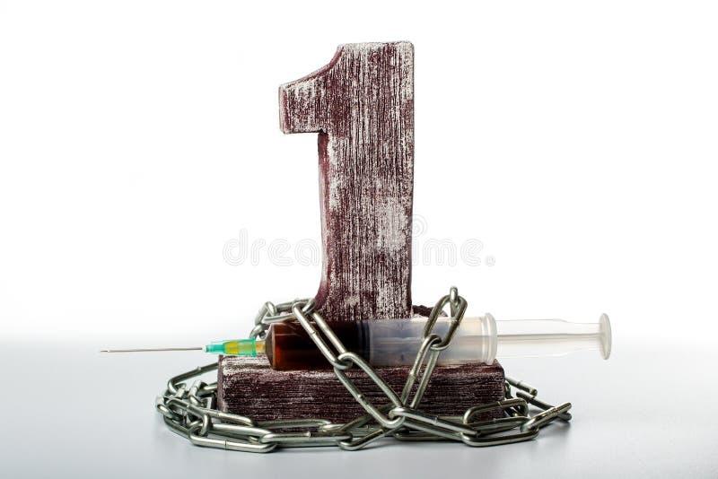 La siringa con il liquido rosso è legata con una catena al numero uno fotografia stock libera da diritti