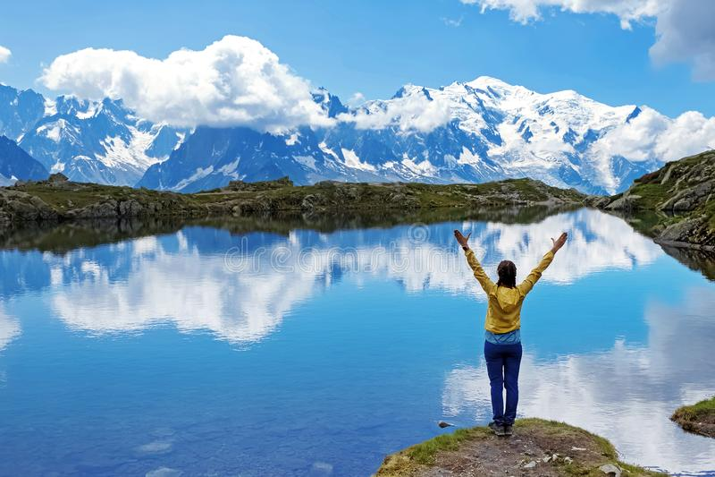 La situación de la mujer joven en la orilla del lago escénico de la montaña en las montañas con sus manos aumentó imagen de archivo libre de regalías