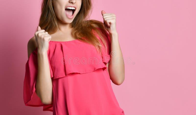 La situación de la señora joven aislada sobre fondo rosado hace gesto del ganador imagenes de archivo
