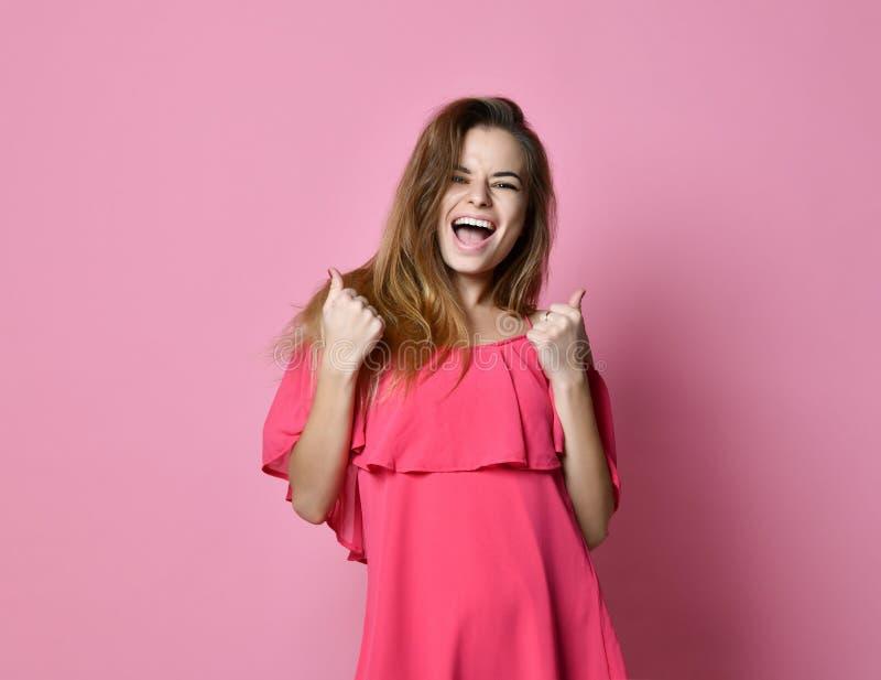 La situación de la señora joven aislada sobre fondo rosado hace gesto del ganador foto de archivo libre de regalías