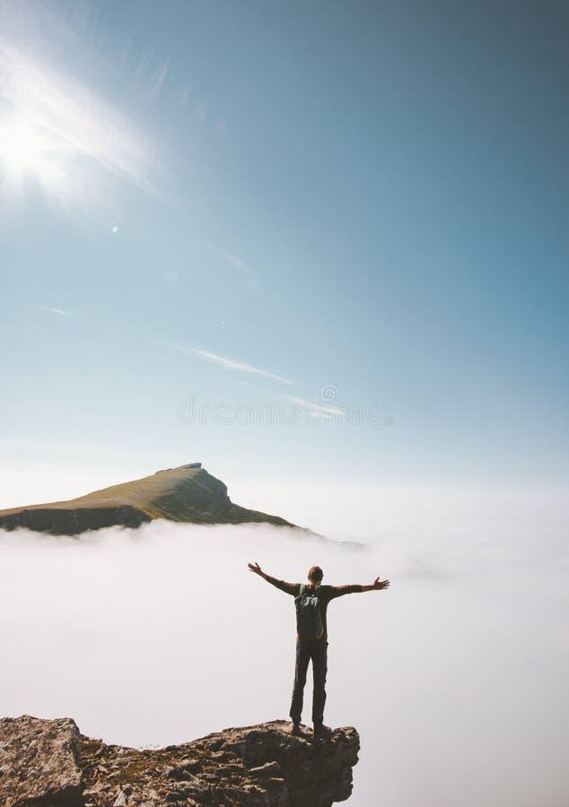 La situación del hombre del caminante sola en el borde del acantilado de la montaña sobre las nubes aumentó las manos imágenes de archivo libres de regalías
