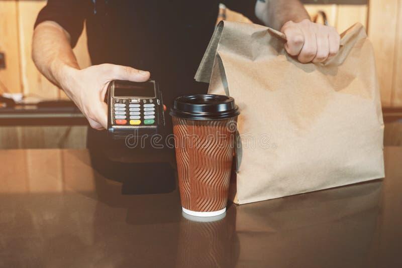 La situación del hombre de Barista detrás de la barra con la bebida caliente del café en la bolsa de papel de la taza de papel y  foto de archivo