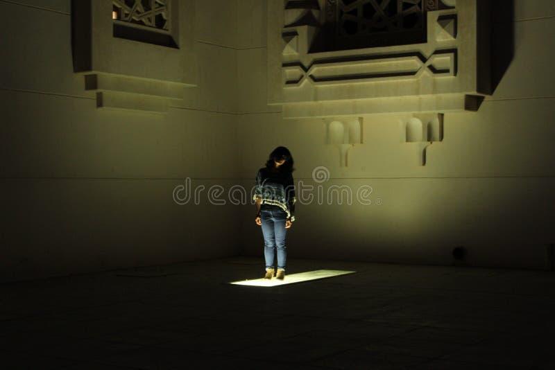 La situación femenina en el área destacada cerca de la arquitectura con mitad de su cara cubrió por una sombra foto de archivo
