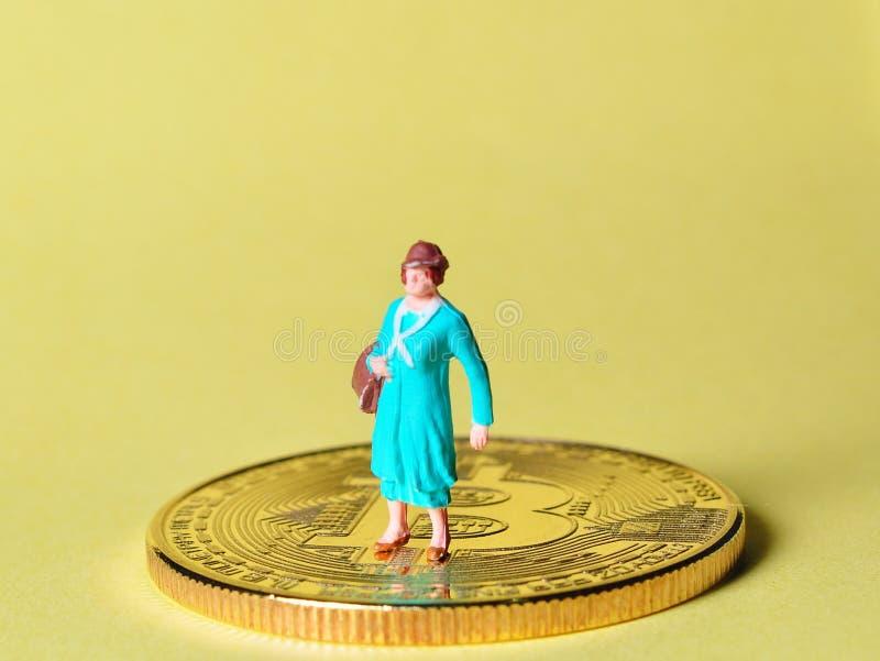 La situación miniatura de la gente en las monedas disfruta de su renta o la gana foto de archivo libre de regalías
