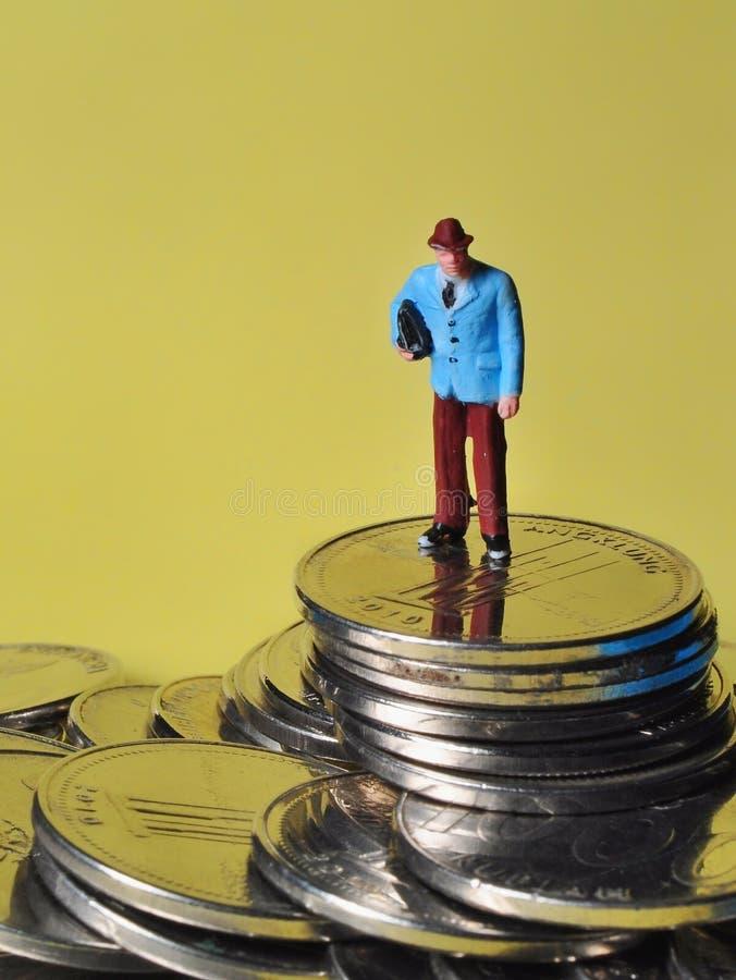 La situación miniatura de la gente en las monedas disfruta de su renta o la gana fotografía de archivo