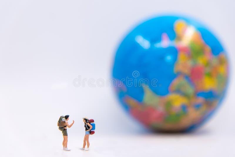 La situación miniatura de la mochila del viajero y del caminante considera el globo para el turista y la aventura en todo el mund fotografía de archivo