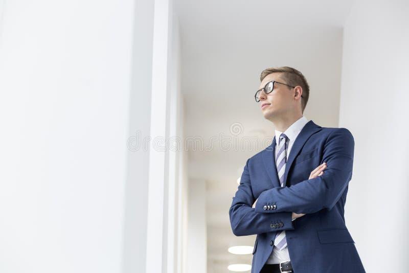 La situación pensativa joven del hombre de negocios con los brazos cruzó la mirada lejos en pasillo de la oficina fotos de archivo