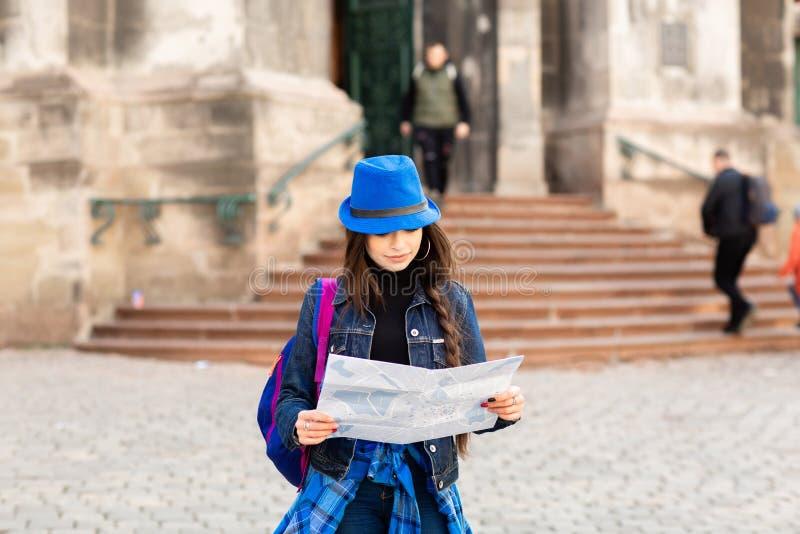 La situaci?n de la mujer joven cerca de la iglesia en la ciudad vieja Lviv, y sostiene un mapa a disposici?n ucrania fotografía de archivo