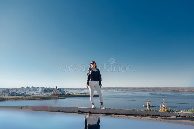 La situaci?n elegante de la muchacha en una monta?a, cielo azul reflej? en el agua foto de archivo