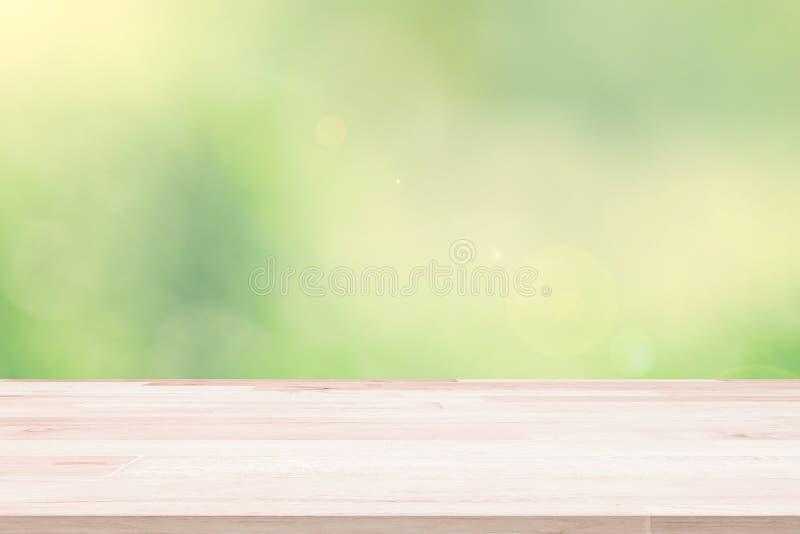 La sobremesa de madera vacía de la cubierta en verde empañó el fondo abstracto del fondo del follaje Listo usado nos exhibición o imagen de archivo libre de regalías
