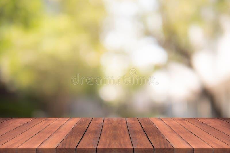 La sobremesa de madera vacía en verde de la naturaleza empañó el fondo en el jardín, espacio para los productos de la demostració imagen de archivo libre de regalías