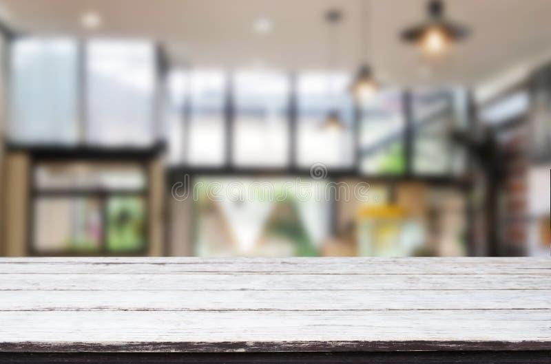 La sobremesa vacía del tablero de madera y empañar interior sobre la falta de definición en fondo de la cafetería, imita para arr foto de archivo libre de regalías