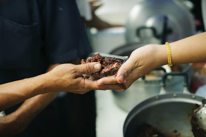 La soci?t? de partager la nourriture au sans-abri et au plus pauvre : Le concept de l'alimentation : Les mains des riches donnent images libres de droits