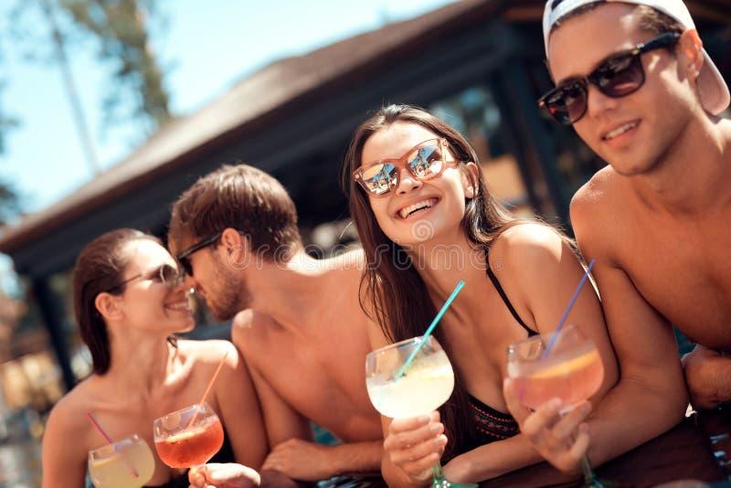La società degli amici felici beve le bevande del cocktail in piscina ad estate Partito di piscina fotografia stock
