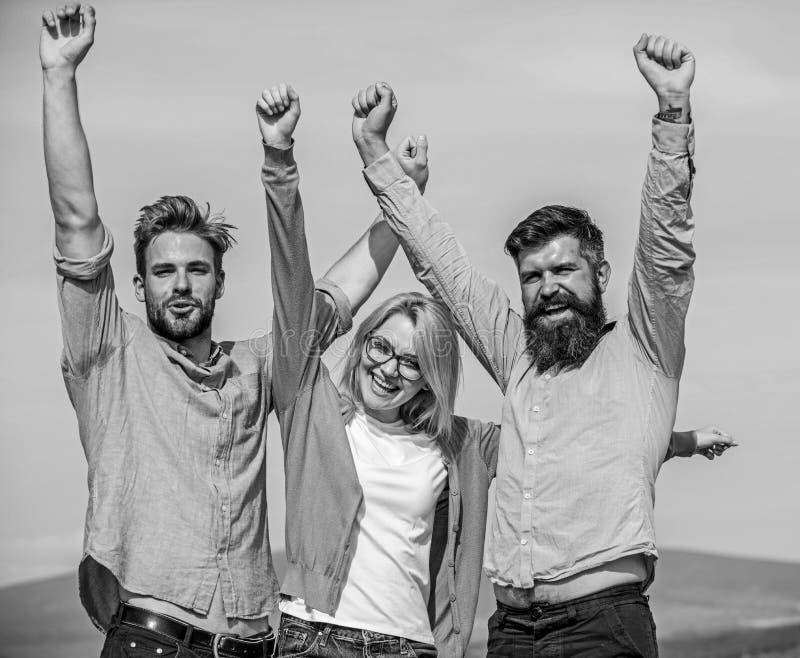 La società ha raggiunto la cima Una società di tre colleghi o partner felici che celebrano successo, fondo del cielo Sfera differ immagini stock libere da diritti