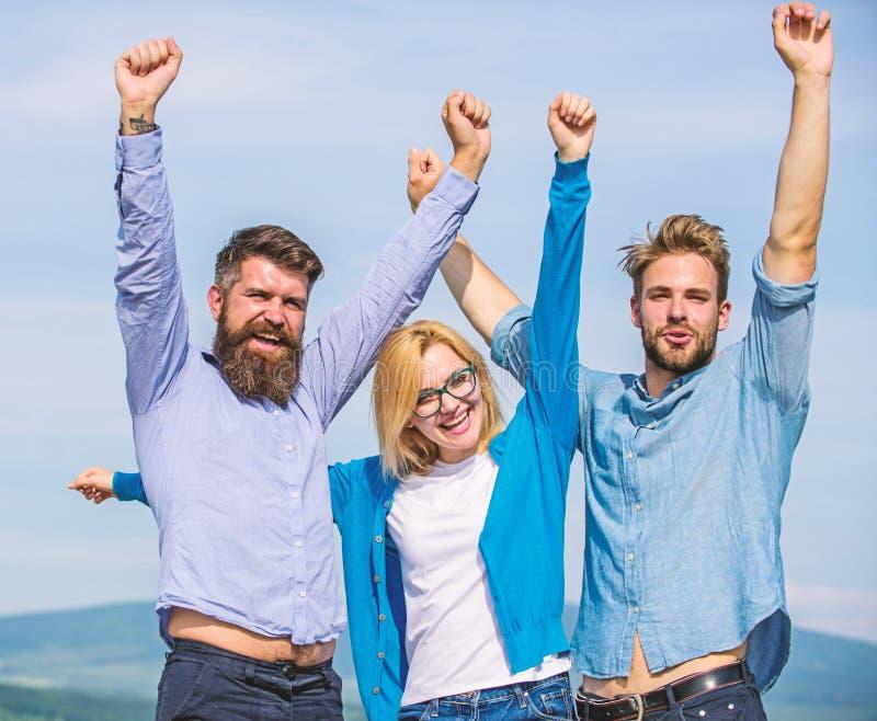 La società ha raggiunto la cima Una società di tre colleghi o partner felici che celebrano successo, fondo del cielo Sfera differ immagine stock