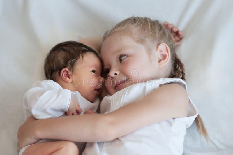 La soeur étreint son jeune frère photo stock