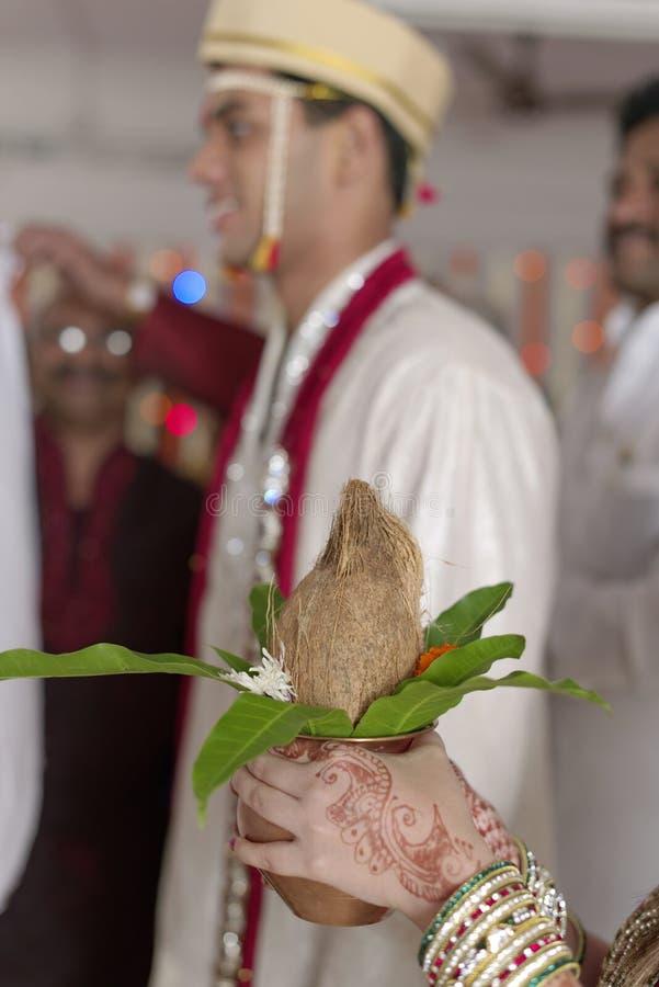 La soeur du marié indou indien avec la noix de coco dans des ses mains au rituel d'échanger la guirlande dans le mariage de mahara images stock