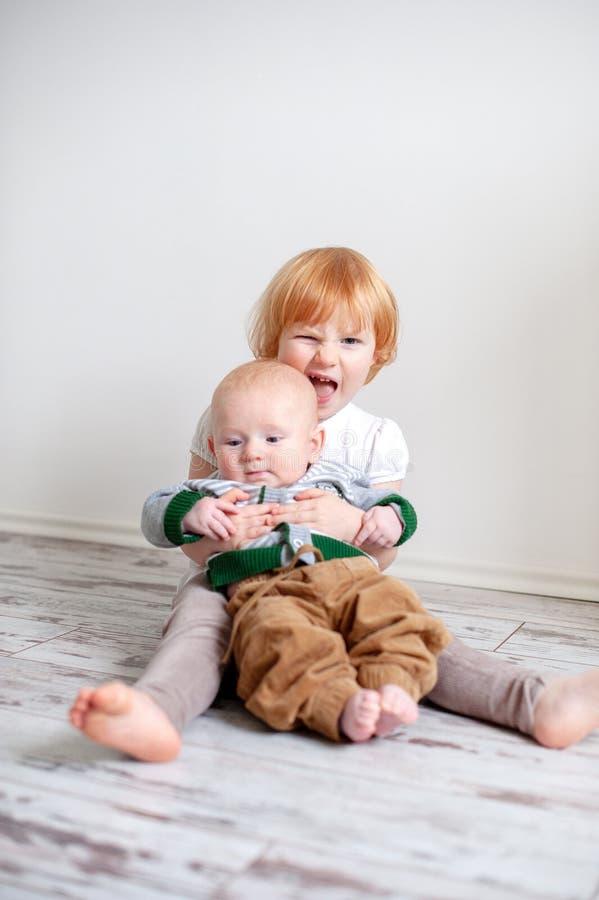 La soeur plus âgée tient un petit frère dans des ses bras photo libre de droits