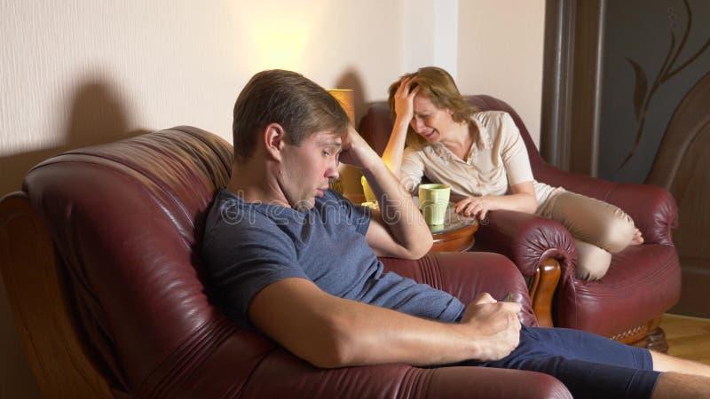 La soirée, le mari et l'épouse de famille se reposent dans une chaise dans leur maison et découvrent les relations image libre de droits
