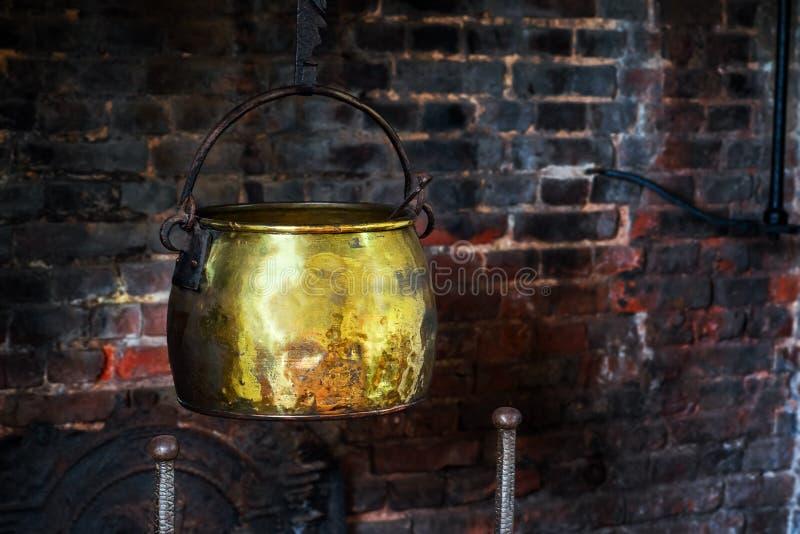 La sola mano antigua 1590 de la caldera del vintage forjada cocinando el pote hangged por el de oro viejo de la chimenea del hoga imagen de archivo