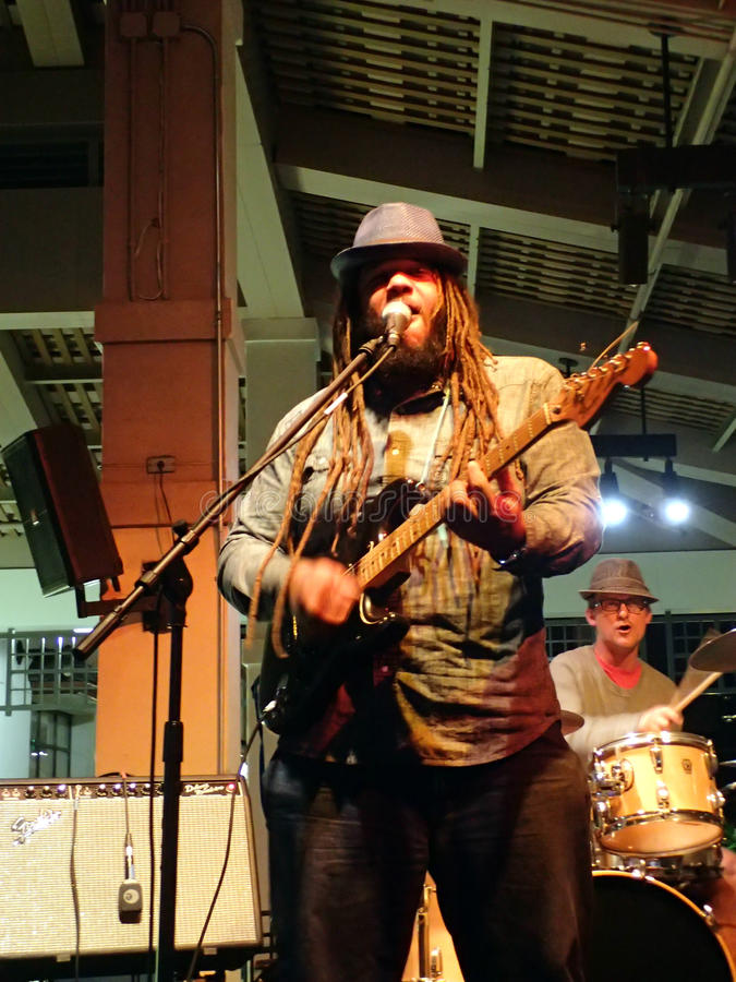 La solista Guidance Band canta nel mic mentre la banda si inceppa in scena fotografia stock