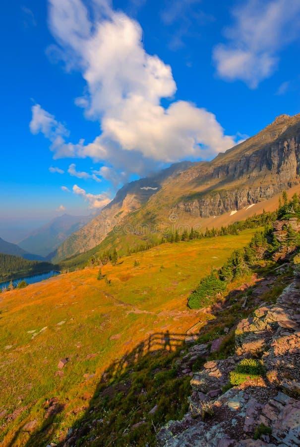 La sombra de caminantes en el lago ocultado pasa por alto el Parque Nacional Glacier imagenes de archivo