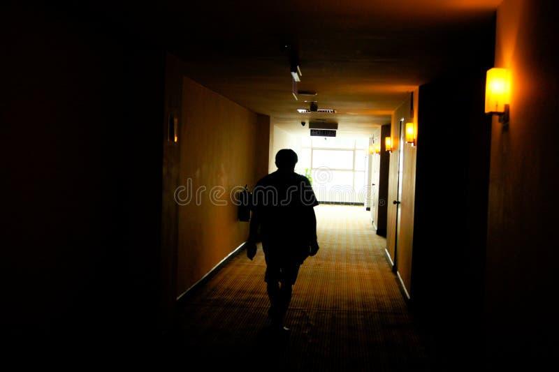La sombra de los hombres que caminan el túnel oscuro y yendo a la luz fotos de archivo