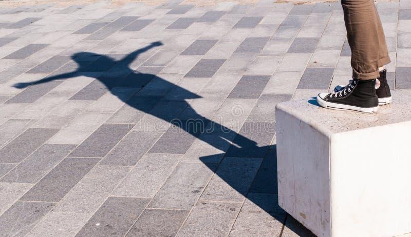 La sombra de una mujer joven con los brazos abiertos proyectó en el pavimento fotos de archivo libres de regalías
