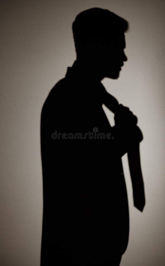 La sombra del hombre en la pared en un traje está enderezando su lazo imagenes de archivo