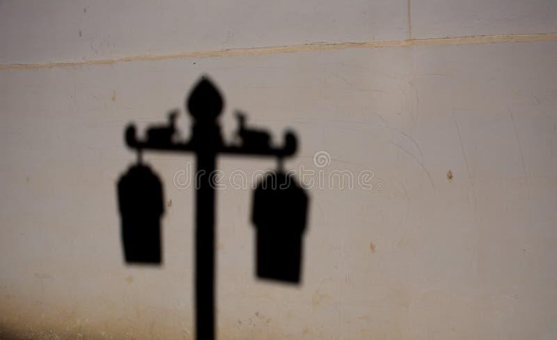 La sombra del poste de la lámpara que tiene una muestra de dos ciervos y ruedas de oro de Dharma en ella en templo del buddhism t imagen de archivo libre de regalías