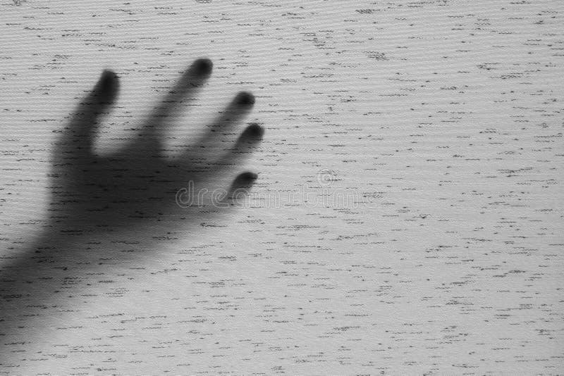La sombra superficial del primer de la mano detrás de la cortina gris de la tela texturizó el fondo con el espacio de la copia en fotos de archivo libres de regalías