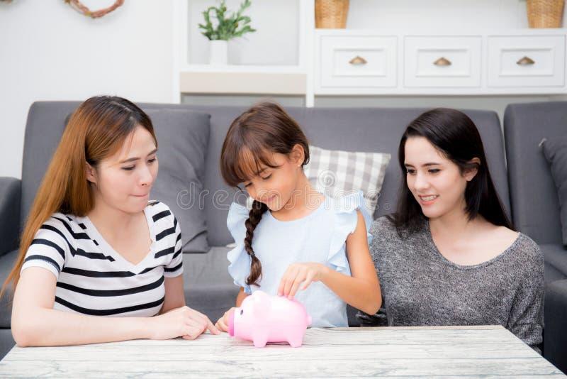 La sonrisa asiática de la madre y de la tía y felices consideran a la hija el poner de la moneda en la hucha para ahorrar imagen de archivo