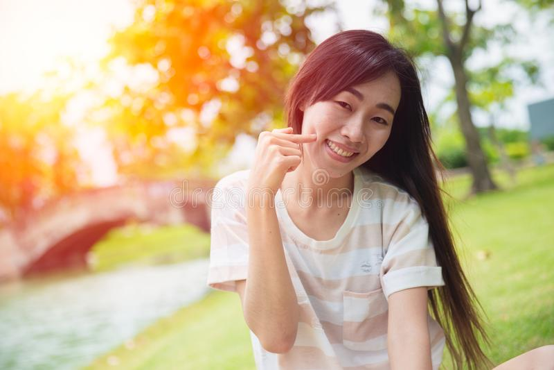 La sonrisa asiática linda de la mujer con el finger forma hoyuelos la mejilla imagen de archivo