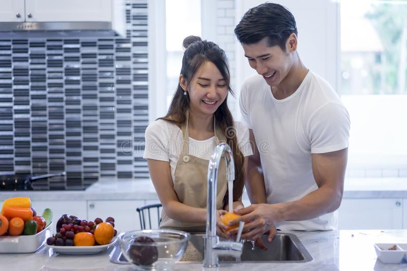 La sonrisa cariñosa de los pares jovenes asiáticos hermosos está mirando al cookin imagen de archivo libre de regalías