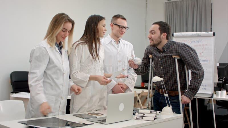 La sonrisa cuida el donante de píldoras al paciente masculino en las muletas y animarlo para arriba fotos de archivo libres de regalías