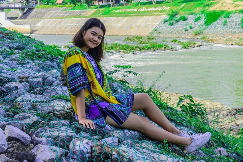La sonrisa de la muchacha y sentarse en el frente de la roca del puente de la presa foto de archivo