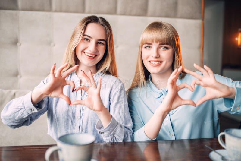 La sonrisa de novias muestra los corazones con los fingeres imagen de archivo