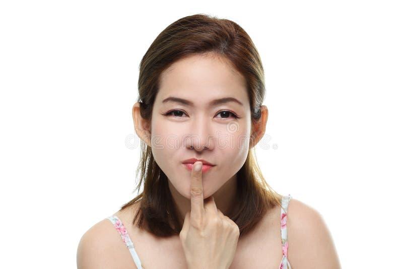 La sonrisa feliz asiática de las mujeres hermosas con los labios glosa y se besa su finger aislado en el fondo blanco fotos de archivo libres de regalías