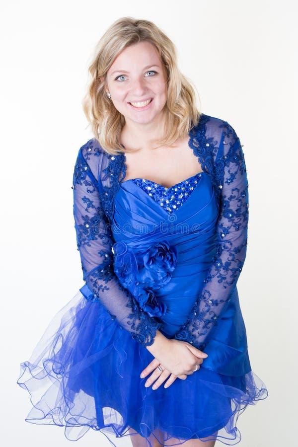 La sonrisa feliz de la muchacha bonita hermosa en estudio en vestido de fiesta azul aisló el fondo blanco fotografía de archivo