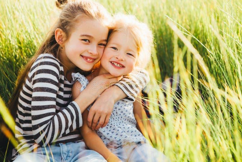 La sonrisa feliz embroma la relajación en hierba verde debajo del sol, espacio de la copia Color-tono aplicado fotos de archivo libres de regalías