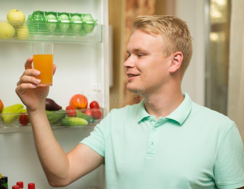 La sonrisa feliz hermosa joven del hombre, celebrando un vidrio de jugo está en el refrigerador imágenes de archivo libres de regalías