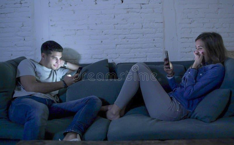 La sonrisa joven del sofá del sofá de los pares en casa feliz junto pero separado ignorándose concentró en el teléfono móvil en I fotografía de archivo libre de regalías