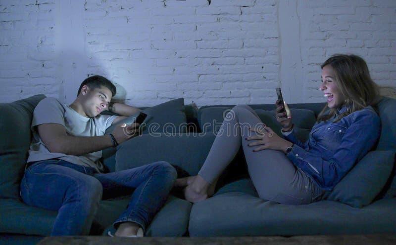 La sonrisa joven del sofá del sofá de los pares en casa feliz junto pero separado ignorándose concentró en el teléfono móvil en I foto de archivo