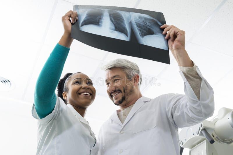 La sonrisa masculina y hembra doctor la radiografía del pecho de Examining en Hospita fotos de archivo libres de regalías